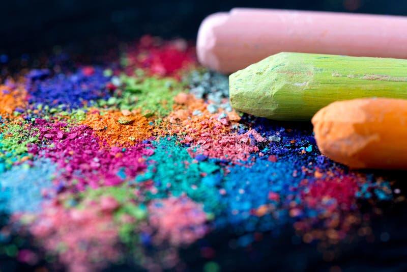 Miettes de craie multicolore sur un fond noir Joie, carnaval, panorama Un jeu pour des enfants Art photographie stock libre de droits
