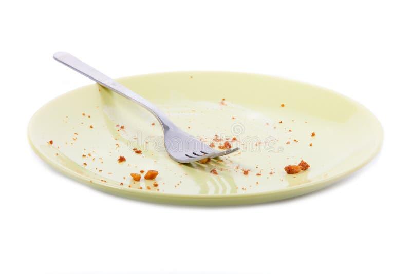 Miettes et fourchette de gâteau de plaque jaune image stock