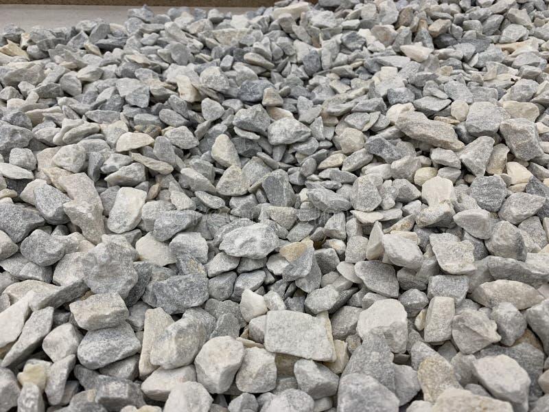 Migalha pequena cinzenta do granito, material de construção, fundo simples foto de stock