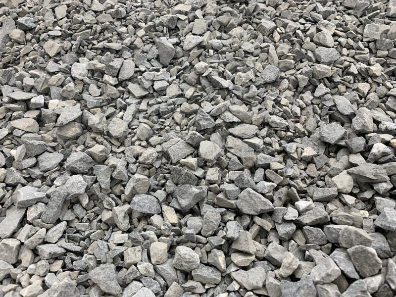 Migalha pequena cinzenta do granito, material de construção, fundo simples imagem de stock