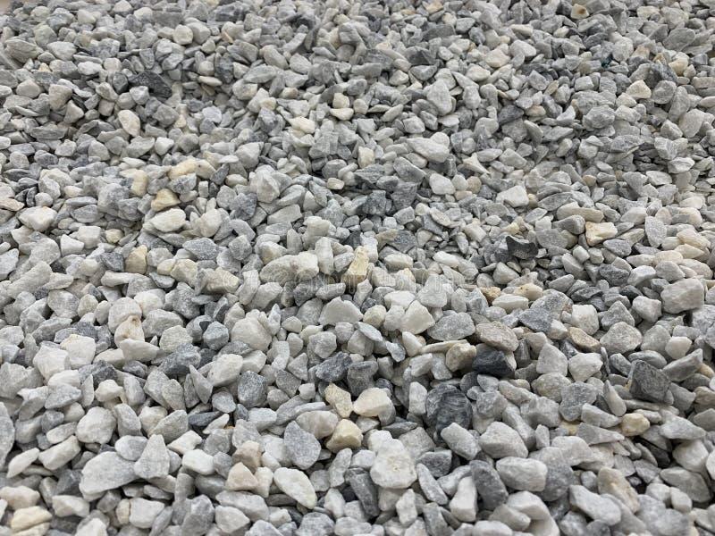 Migalha pequena cinzenta do granito, material de construção, fundo simples fotografia de stock