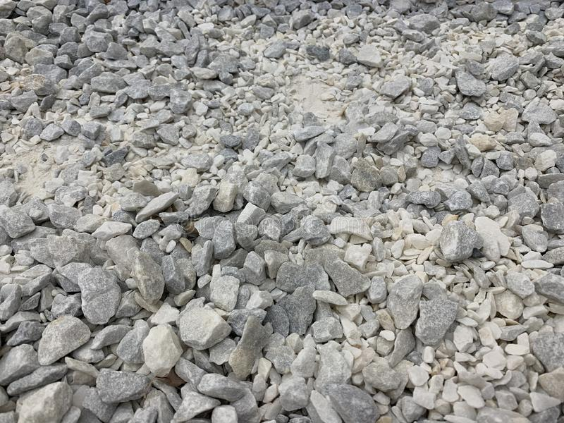 Migalha pequena cinzenta do granito, material de construção, fundo simples imagens de stock
