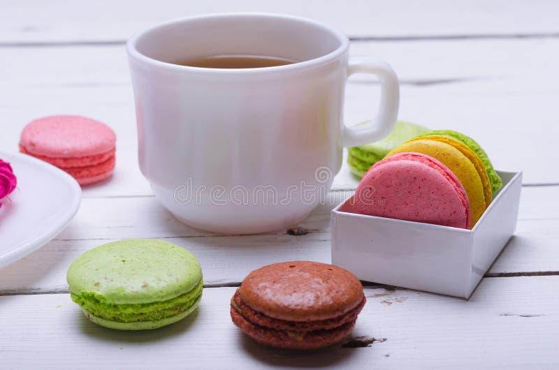 Migdałowi ciastka i filiżanka herbata na drewnianym bielu stole fotografia stock