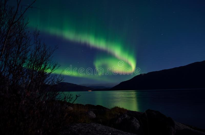 Mighty aurora borealis dancing on night sky over mountain and fjord landscape stock photography