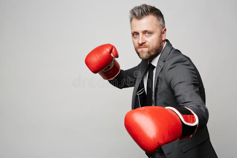 Mighty boss. Businessman in boxing gloves attacking his rival royalty free stock photo