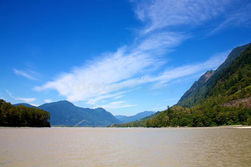 The mighty Fraser River. The waters of the mighty Fraser River in British Columbia Canada with a backdrop of a large coastal mountain royalty free stock photography