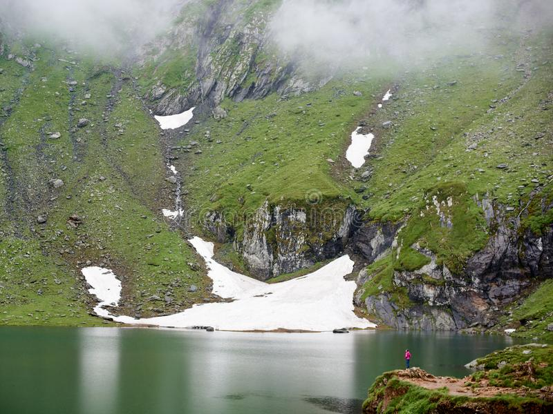 Mighty mountains are covered fog and lake at foot, Romania royalty free stock photography