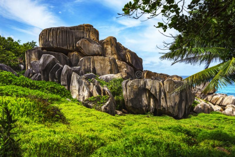 Mighty red granite rocks in lush green grass at anse songe, la d. Hiking a footpath in the wilderness to mighty red granite rocks in lush green grass at anse royalty free stock photo