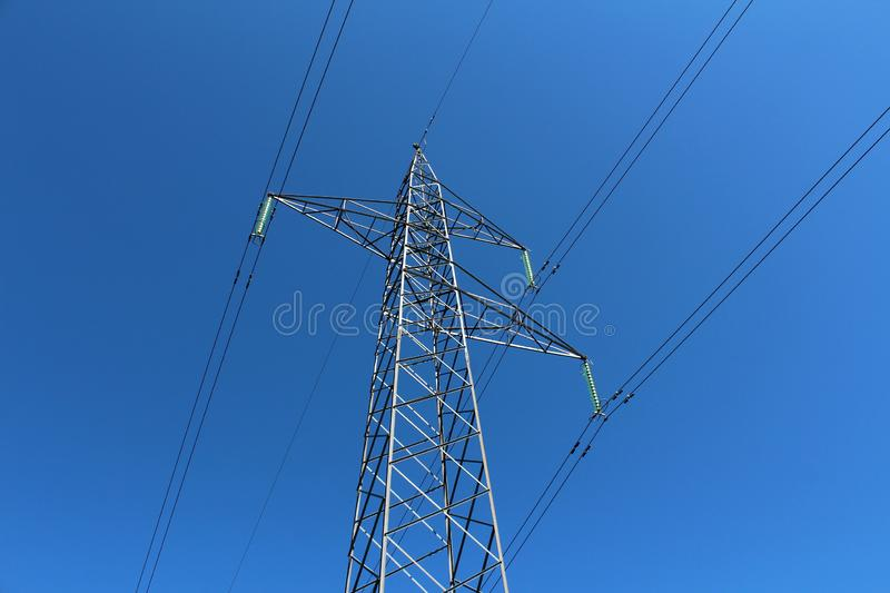 Mighty tall power line utility pole made of strong metal pipes with multiple electrical wires connected with glass insulators on stock photography