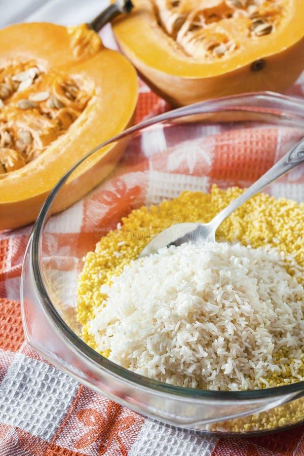 Miglio e riso lavati crudi in una pentola di vetro nel corso della preparazione del porridge del latte con la zucca e l'uva passa fotografia stock
