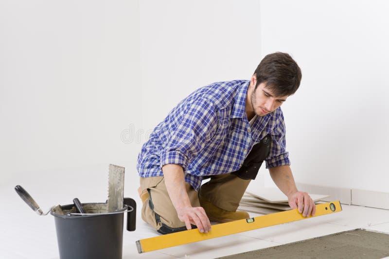 Miglioramento domestico delle mattonelle - tuttofare con il livello immagine stock