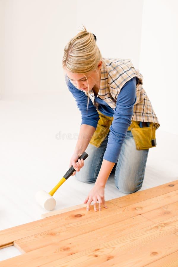 Miglioramento domestico - donna che installa pavimento di legno fotografia stock libera da diritti