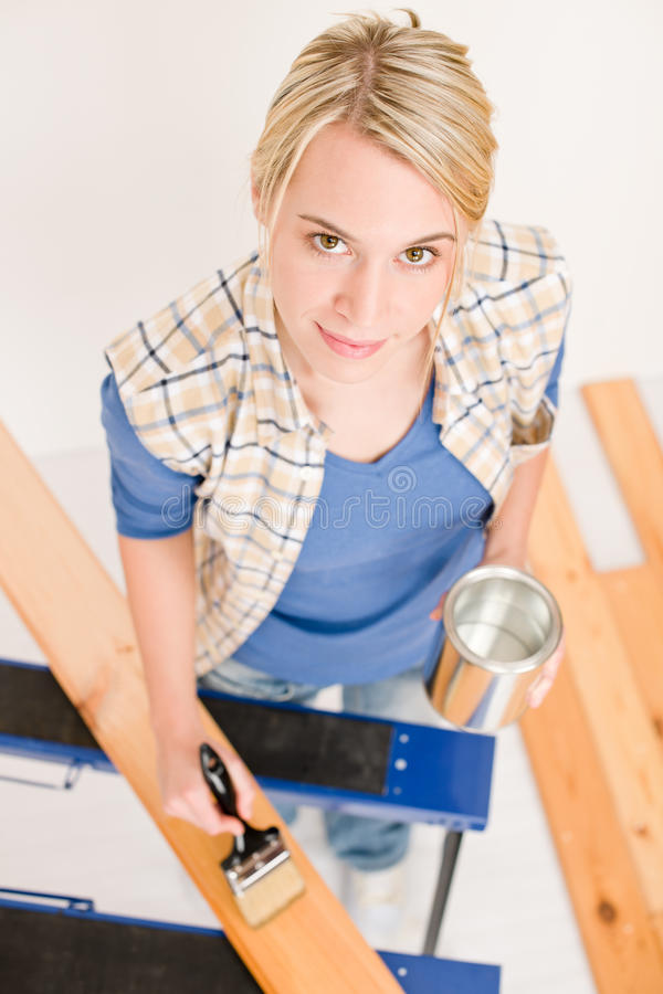 Miglioramento domestico - donna che vernicia plancia di legno immagine stock