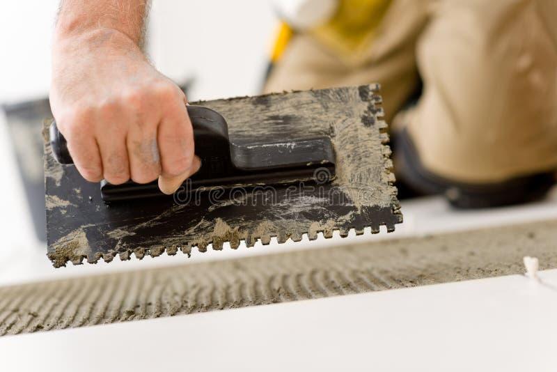 Miglioramento domestico, il rinnovamento - equipaggi la stenditura delle mattonelle immagine stock