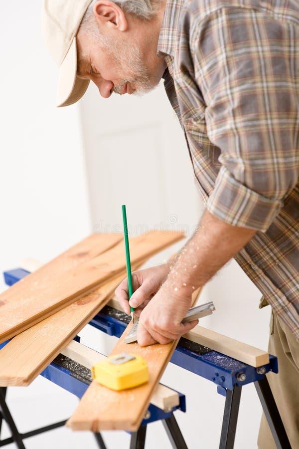 Miglioramento domestico - il tuttofare prepara il pavimento di legno immagine stock