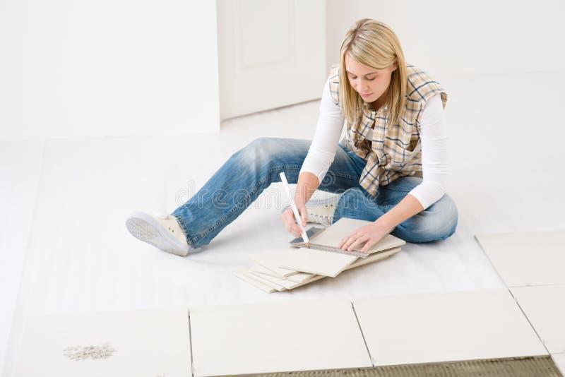 Miglioramento domestico - mattonelle di misurazione handywoman immagini stock