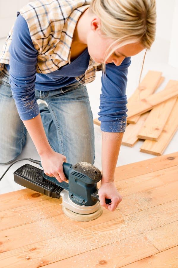 Miglioramento domestico - pavimento di legno di smeriglitatura handywoman fotografia stock libera da diritti