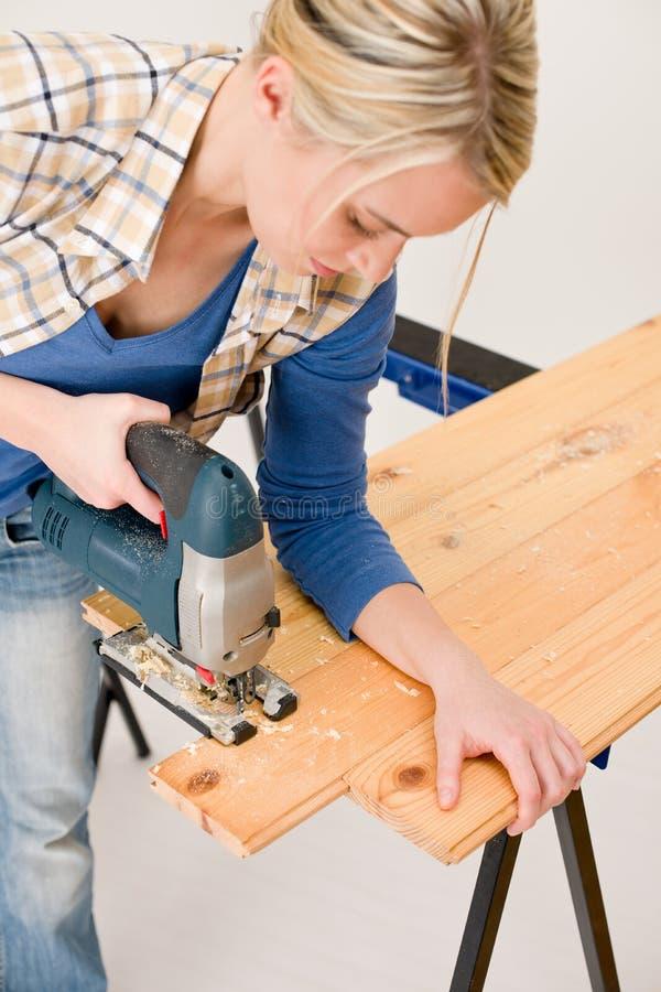 Miglioramento domestico - pavimento di legno di taglio handywoman fotografie stock