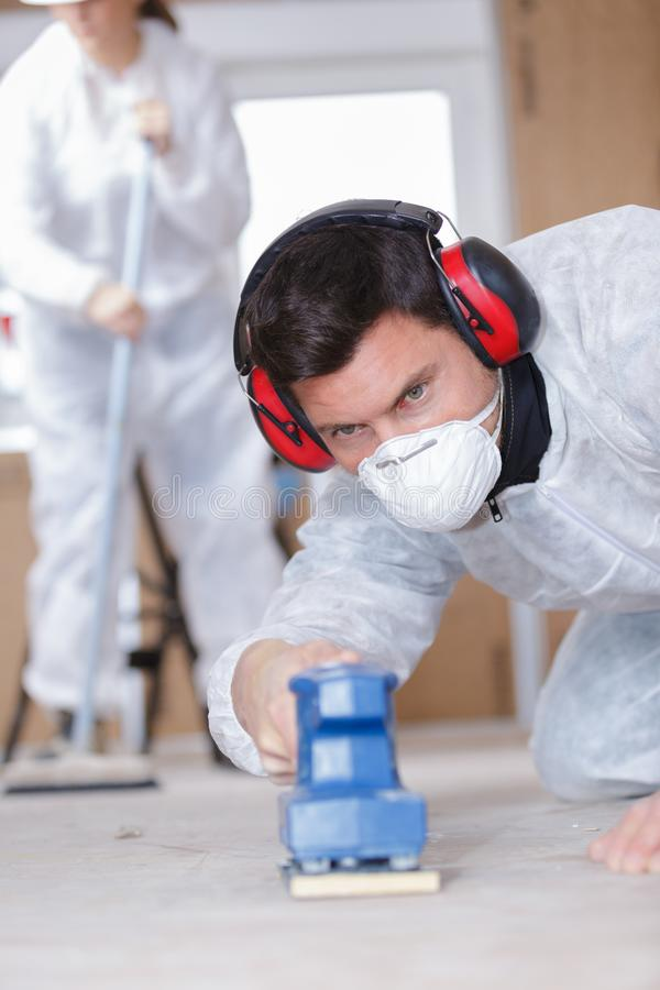 Miglioramento domestico - tuttofare che insabbia pavimento di legno in officina immagine stock