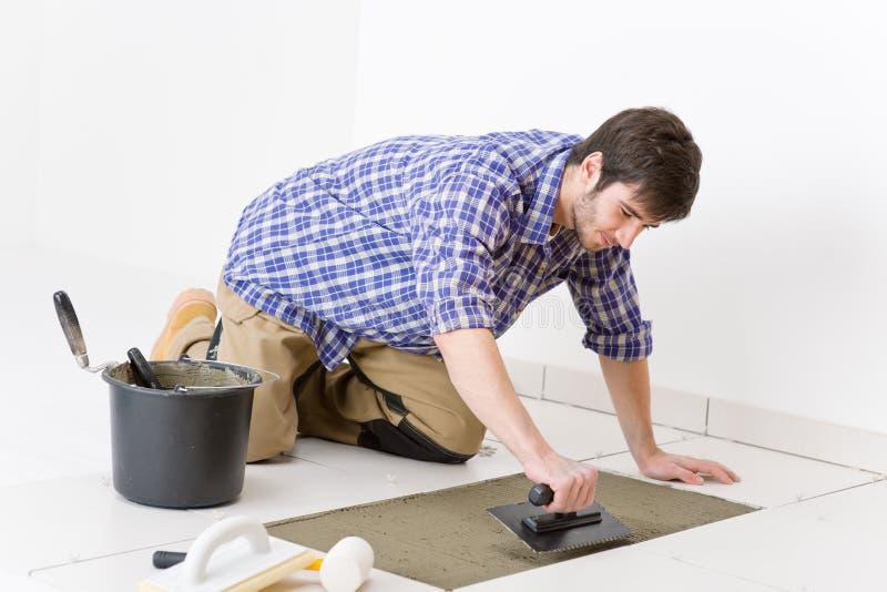 Miglioramento domestico - tuttofare che pone mattonelle fotografie stock