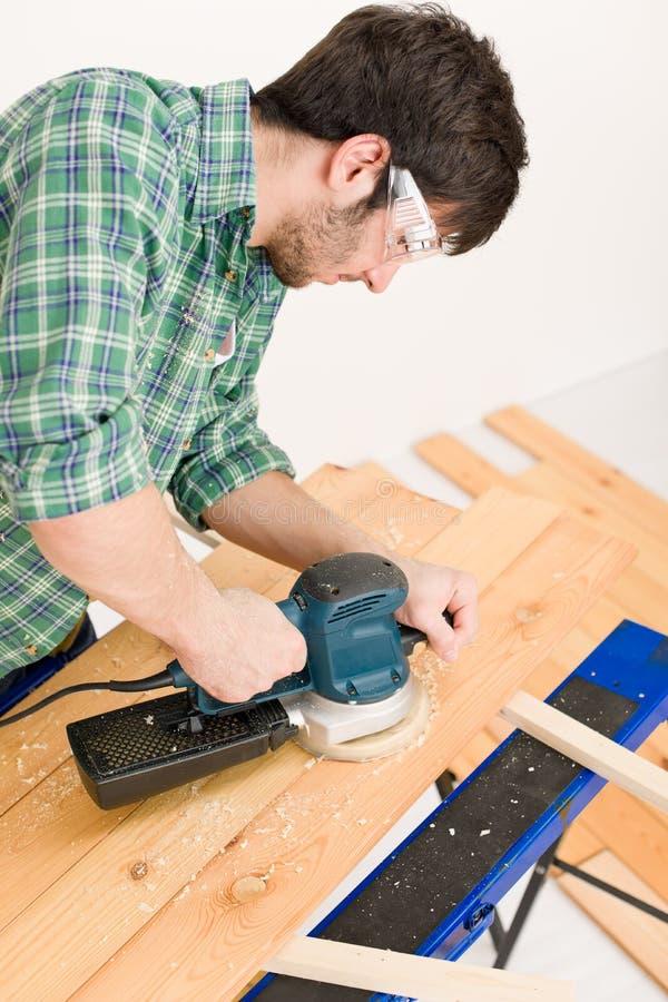 Miglioramento domestico - tuttofare che smeriglia pavimento di legno fotografia stock libera da diritti