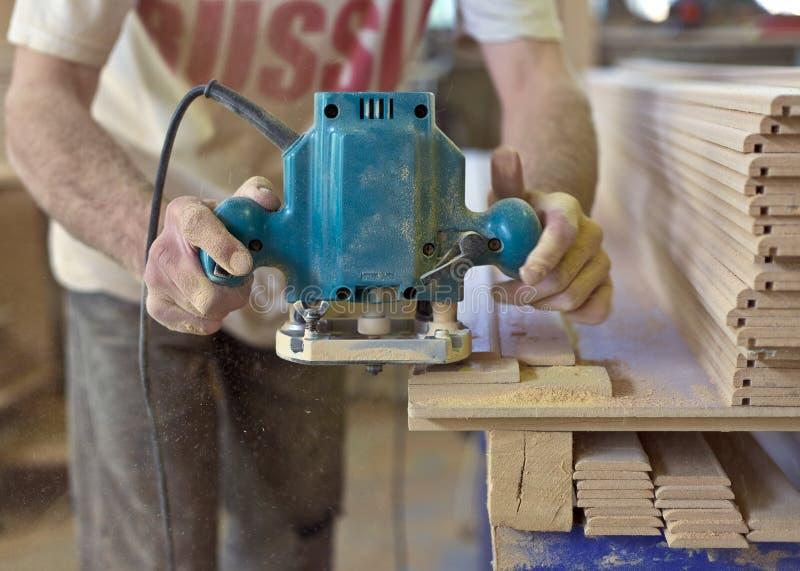Miglioramento domestico - tuttofare che smeriglia pavimento di legno fotografia stock