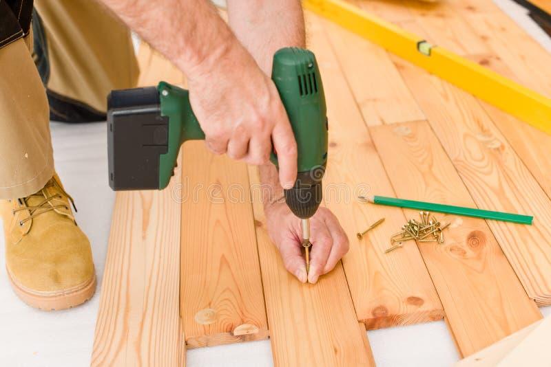 Miglioramento domestico - uomo che installa pavimento di legno fotografia stock