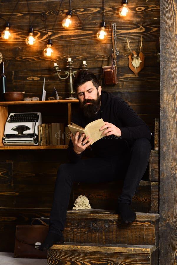 Migliore fine settimana L'uomo con la barba tiene il vecchio libro ed ha letto Tipo in atmosfera calda accogliente che si rilassa fotografia stock