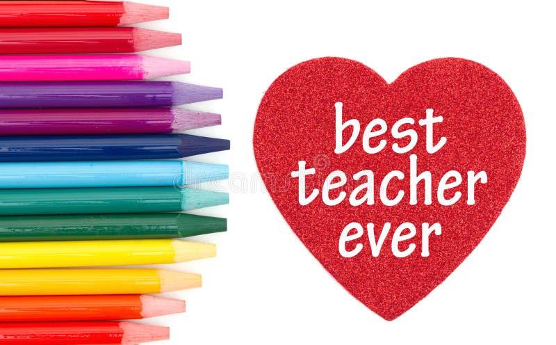 Migliore messaggio dell'insegnante mai su cuore rosso con le matite colorate dell'acquerello fotografie stock libere da diritti