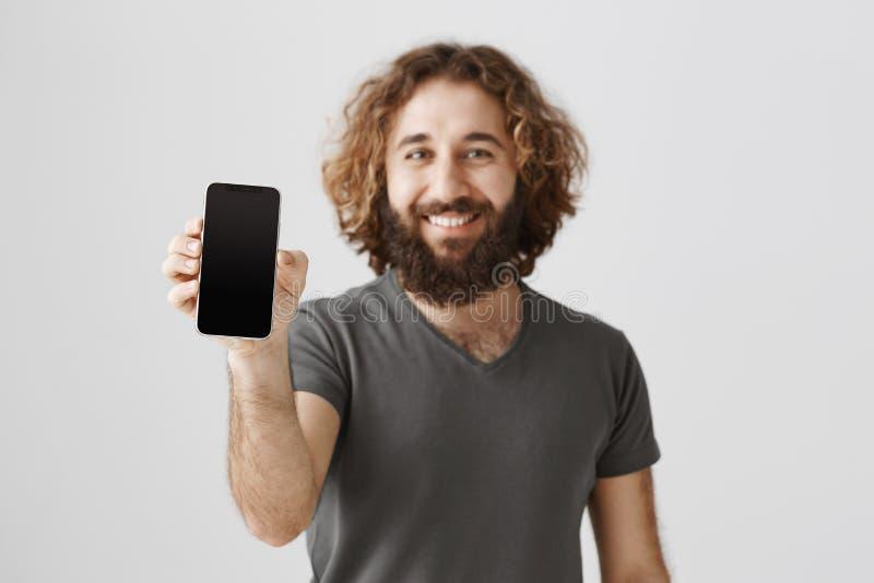 Migliore scelta per la gente di affari Lo studio ha sparato dell'uomo arabo bello piacevole che mostra lo smartphone mentre stava immagine stock