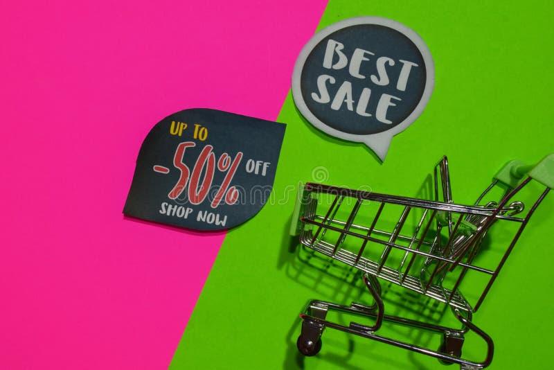 Migliore vendita e fino a -50% fuori dal testo e dal carrello del negozio ora Concetto di affari di promozione e di sconto su fon immagine stock libera da diritti