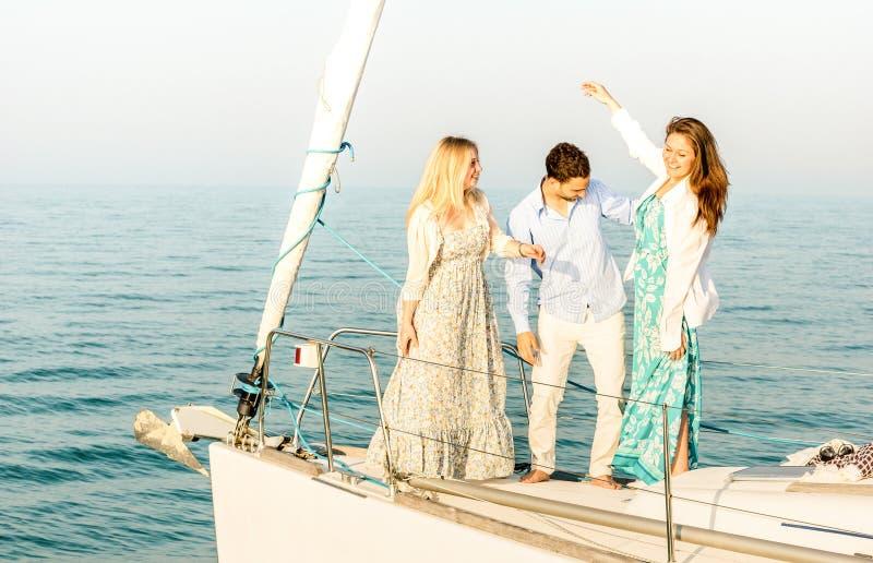 Migliori amici che ballano e che si divertono sulla barca a vela di lusso esclusiva - concetto di viaggio di amicizia con i giova immagine stock