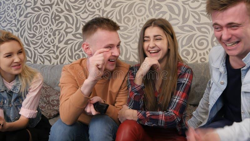 Migliori amici che si siedono sul sofà, godenti e discutenti del film della commedia immagini stock