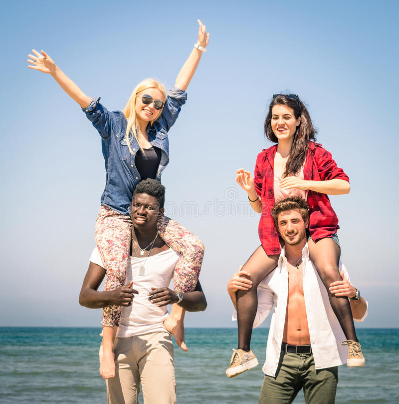 Migliori amici multirazziali alla spiaggia divertendosi con il gioco di a due vie fotografie stock
