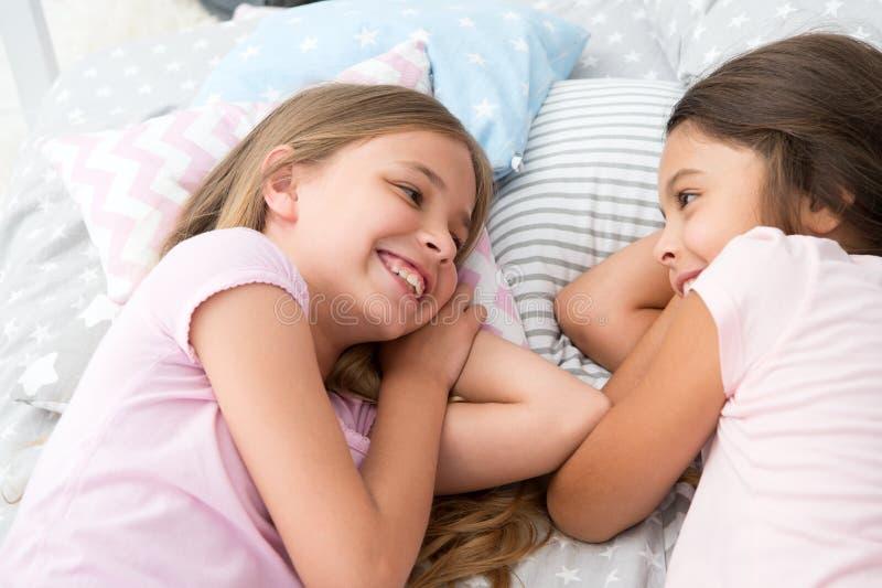 Migliori amici per sempre Ragazze che si rilassano sul letto Concetto del pigiama party Le ragazze vogliono appena avere divertim fotografie stock libere da diritti