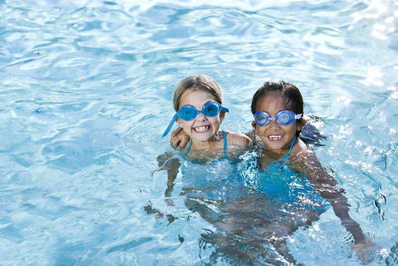 Migliori amici, ragazze che sorridono nella piscina immagini stock libere da diritti
