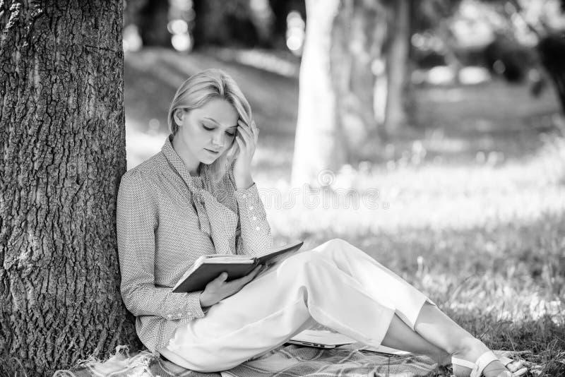Migliori libri di autonomia per le donne La ragazza concentrata si siede il parco che il tronco di albero magro ha letto il libro fotografia stock libera da diritti
