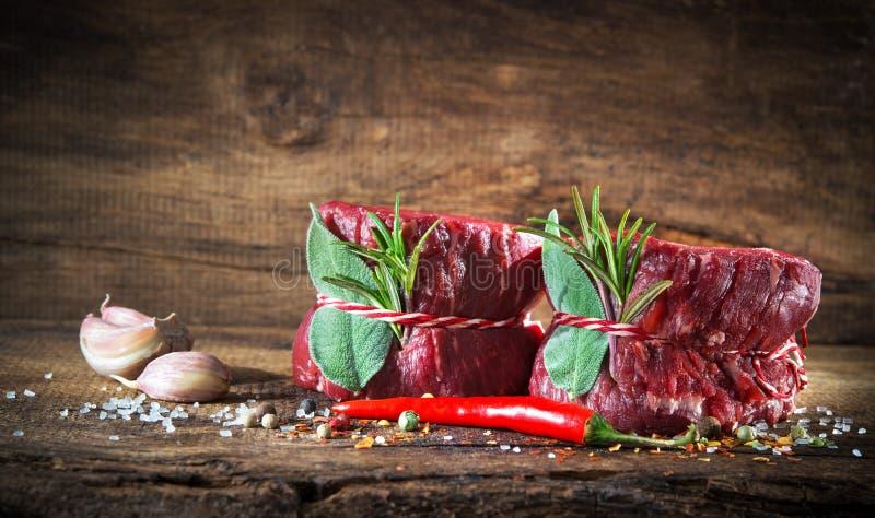 Mignon cru dos bifes de vaca da carne no fundo de madeira imagens de stock