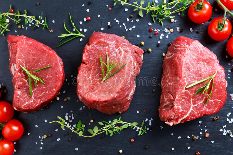 Mignon crudo fresco della bistecca di manzo, con sale, granelli di pepe, timo, pomodori fotografia stock libera da diritti