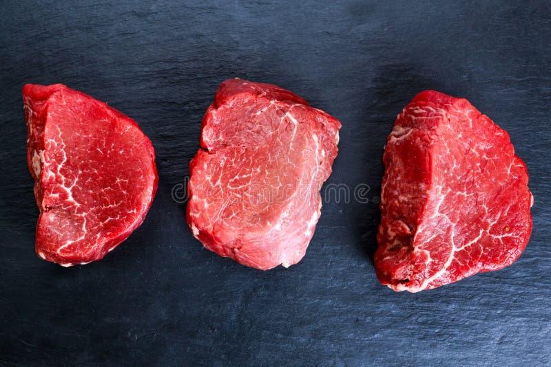 Mignon crudo fresco della bistecca di manzo sul fondo scuro blu del bordo, fotografie stock libere da diritti