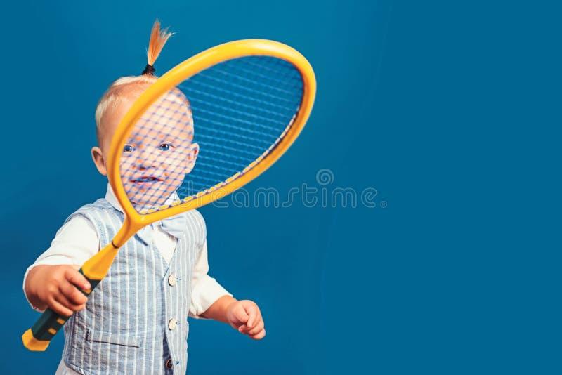 Mignon et énergique Peu amant de sport Petit enfant adorable avec la raquette de tennis Enfant heureux actif Petit tennis photo libre de droits