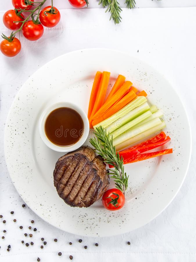 Mignon steak with demi-glace sauce. Served with vegetables stock image