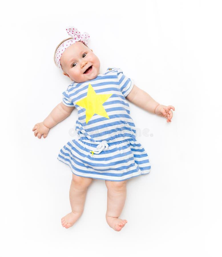 Mignonne petite fille allongée sur un fond blanc portant une robe rayée avec une grande étoile jaune photo stock