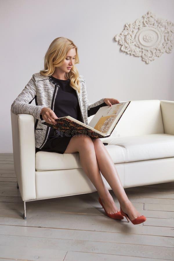 Mignons blonds amincissent la femme convenable d'affaires dans la robe noire et les clas gris photo stock