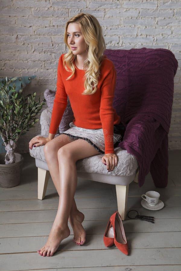 Mignons blonds amincissent la femme convenable d'affaires dans le sourire orange de chandail C photographie stock libre de droits