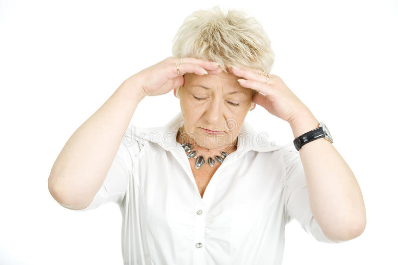Migraine. Frustrated woman with her hands on the forehead royalty free stock images