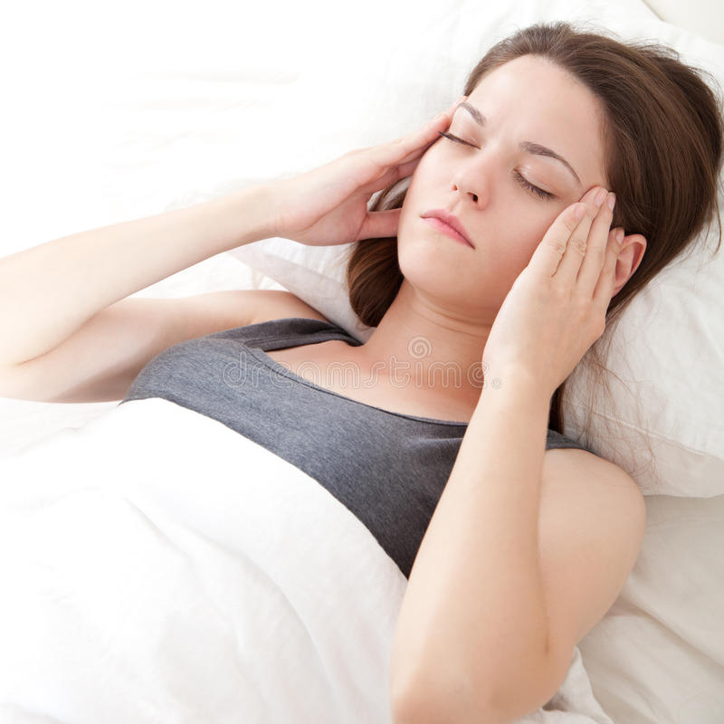 Migraine. Beautiful young woman lying in bed and having migraine stock photos