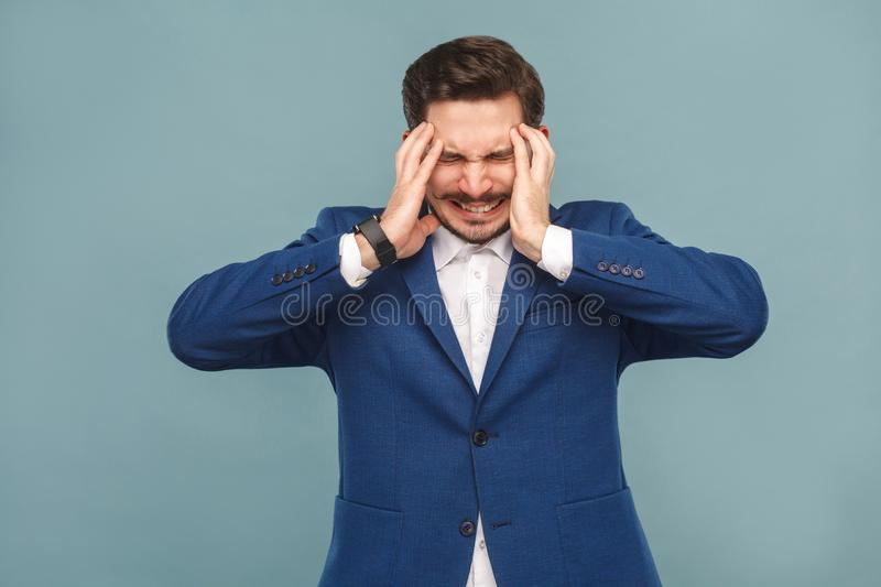 Migraine. Boss have headache pain. Migraine. man with headache pain. portrait of handsome bearded man in blue suit and white shirt, with smart watch. Indoor royalty free stock photo