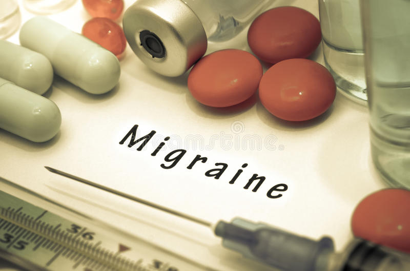 Migraine. Diagnosis written on a white piece of paper. Syringe and vaccine with drugs royalty free stock photo