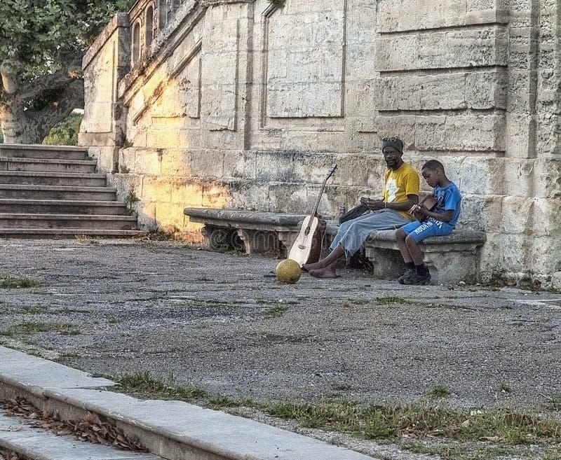 Migranten in Europa De vader onderwijst om het gitaar zwarte kind op de straat in Montpellier, Frankrijk te spelen stock afbeelding